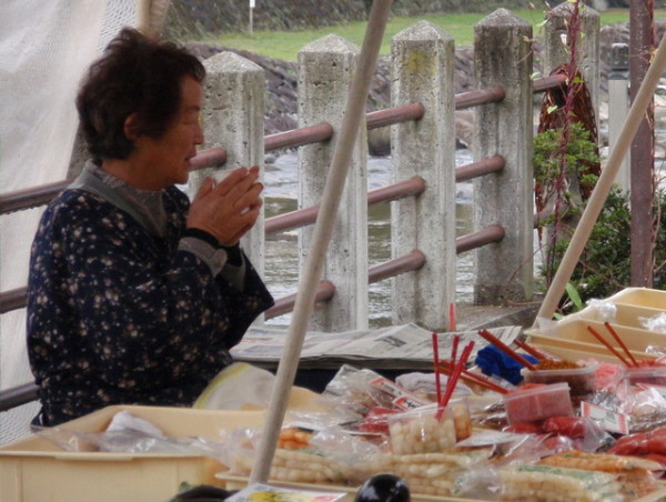 A woman warms up with a hot drink, most likely tea, at a street market in Takayama, a mountain town in Japan